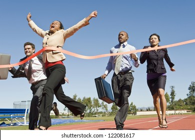 Motion blur shot of a cheerful business woman crossing the finish line with colleagues running in the background