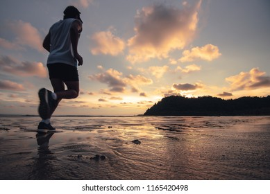 Motion blur of silhouette runner jogging along the beach with shadow reflection on water at sunset golden hour. Healthy lifestyle and exercise for cardio sport training.