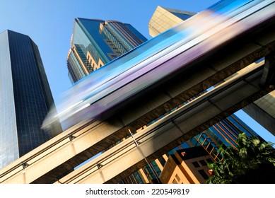 Motion blur of a skytrain speeding through a modern business district.