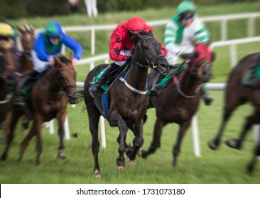 Motion blur speed effect on race horses and jockeys galloping on the race track