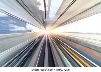 Motion blur of speed train moving in tunnel with light at end.