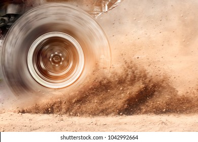 Motion blur of the wheels tires and off-road that goes in the dust of the desert through the wheels on the sand