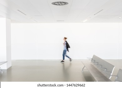 Motion blur of woman walking at contemporary white empty hallway.