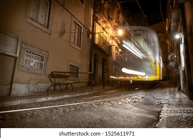 Motion blur of the yellow tram 28 driving along Lisbon's old street. Long exposure at night. Lisbon tram in movement