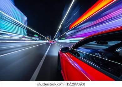 Motion blured View from Side of a Red Muscle Car moving in a night city, Blured road with lights with car on high speed. Concept rapid rhythm of a modern city.