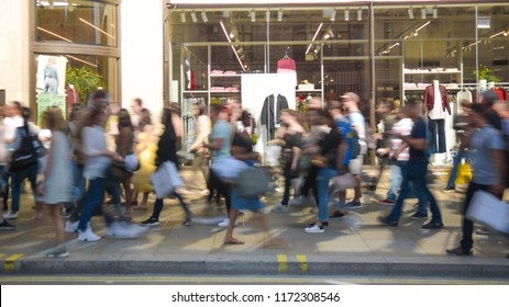 Motion blurred anonymous crowds of people on busy shopping street during a weekend
