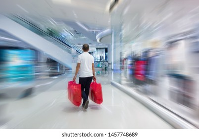Motion Blurred of Asian middle edge man holding red shopping bags in shopping mall. Back of handsome Thai people in white t-shirt walking in fashion shop in department store. Lifestyle concept.