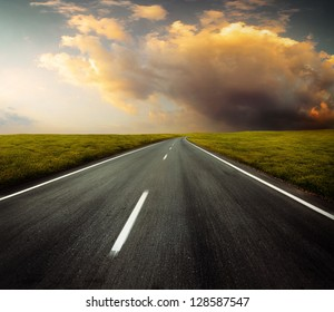 Motion blurred asphalt road through green meadow with sunset cloudy sky on the background
