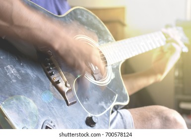 motion blurred background of guy playing guitar with lens flare