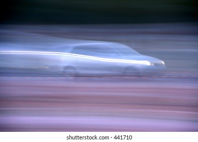 Motion blurred car. Blue toned