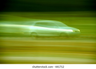 Motion blurred car. Green toned