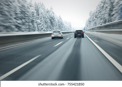 Motion blurred cars overtaking on slippery and frozen highway. Personal perspective used.