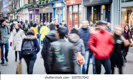 Motion blurred crowd of shopping walking on busy fashion shop street