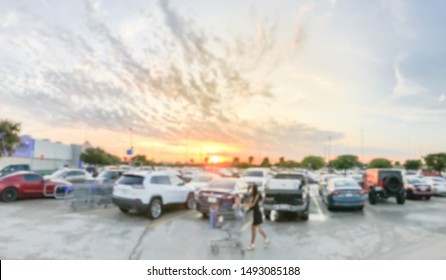 Motion blurred customer with shopping cart walking at parking lots of grocery store near Dallas, Texas, America. Beautiful and dramatic sunset cloud