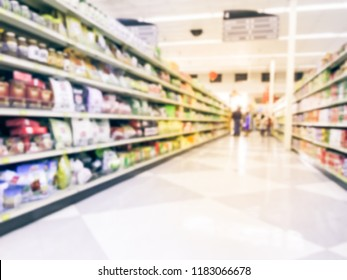 Motion blurred customer shopping for coffee, tea, herbal remedies and canned food aisle at Asian store in Dallas, Texas, US. Wide defocused view of supermarket shelves, variety of products on display