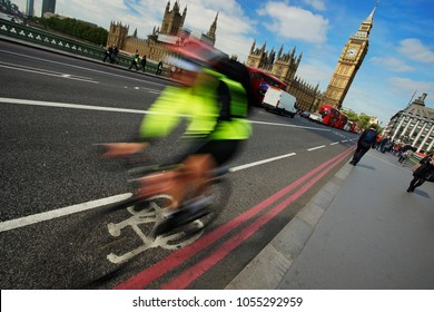 Motion blurred fast moving London bicycle commuter on their way to work crossing Westminster Bridge. Famous Big Ben, blue sky, bicycle lane, traffics and people present in the background.