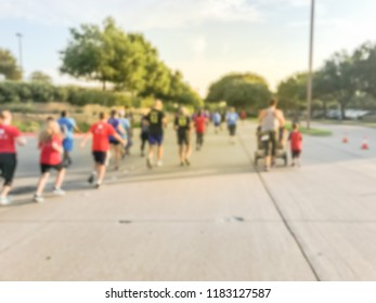 Motion blurred group runners of all abilities at 5K Corporate Challenge race in Richardson, Texas, US. Fitness and healthy lifestyle concept. Athletes running on the roads. Urban sport event abstract