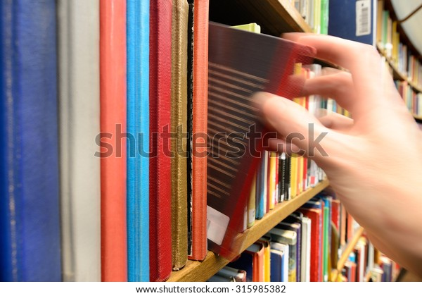 Motion Blurred Hand Picking Book Library Stock Photo (Edit