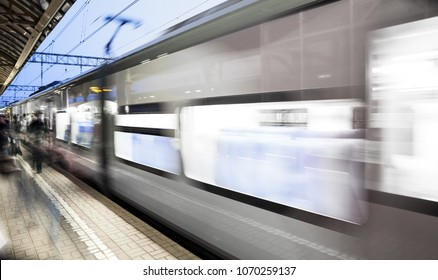 Motion blurred high speed moving passenger commuter railroad train at railway station or subway platform
