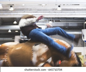 motion blurred image of cowboy riding a crazy mechanical horse for fun