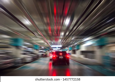 Motion Blurred of parking garage in shopping mall. Underground of car park with cars in business building. Blured image of parking lot in a basement of department store.