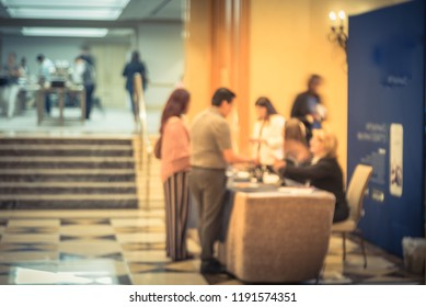 Motion blurred participants check-in at registration table of workshop in hotel lobby near marble grand staircase. Multiethnic people sign-up and received instruction, event package from support staff