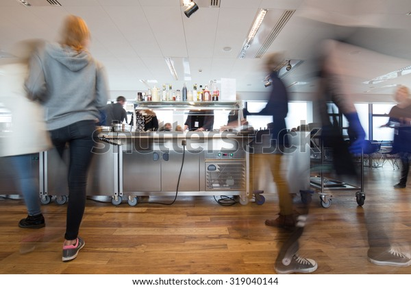 Motion blurred people at lunchtime in a busy canteen