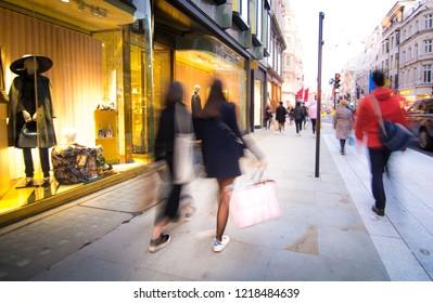 Motion blurred people walking on luxury shopping street