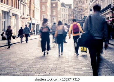 Motion blurred people walking on busy city shopping street