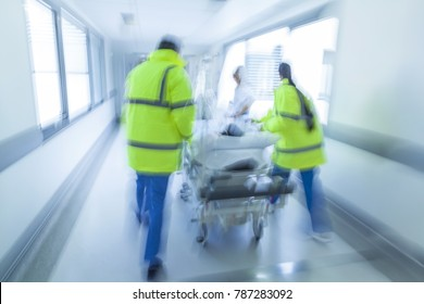 A motion blurred photograph of a child patient on stretcher or gurney being pushed at speed through a hospital corridor by doctors, paramedics and nurses to an accident and emergency room