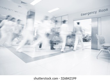 A motion blurred photograph of a patient on stretcher or gurney being pushed at speed through a hospital corridor.