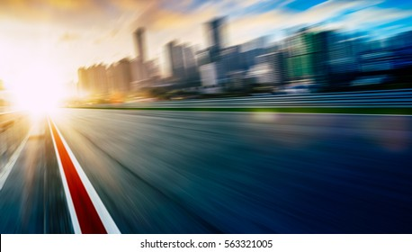 Motion blurred racetrack with city skyline background.