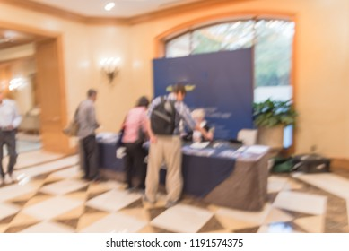 Motion blurred rear view diverse participants at registration check-in workshop table. Multiethnic people sign-up at conference hotel lobby and received instruction, event package from support staff