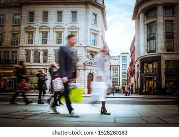 Motion blurred shoppers on busy city street