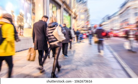 Motion blurred shoppers walking on busy high street