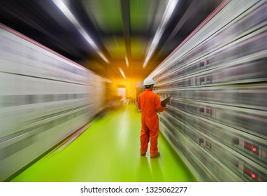 Motion blurred and Soft focus of Engineer checking and monitoring the electrical system in Electrical switch gear at Low Voltage motor control center cabinet room,Electrical selector ,button switch.