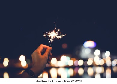 Motion Blurred Sparklers in blur woman hand holding at night city with bokeh reflect on river side, vintage film grain style.Abstract blur sparklers for celebration christmas,festival party background