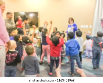 Motion blurred story time at public library in Texas, America. Group of mixed race children and parents dancing and pop bubbles with teacher