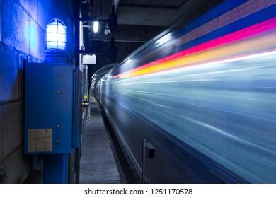 Motion blurred subway train travelling through an underground tunnel.