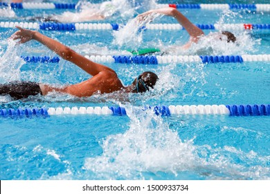Motion blurred swimmers in a freestyle race, focus on lane line and water drops