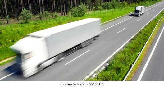 Motion blurred trucks on highway. Transportation industry metaphor