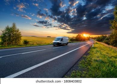 Motion unscharroter weißer Lieferwagen auf der Asphaltstraße in ländlicher Landschaft in den Strahlen des Sonnenuntergangs mit dunkler Sturmwolke