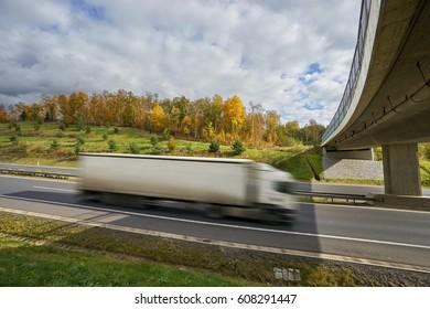 Motion blurred white truck entering under a bridge on a highway in autumn landscape