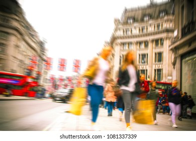 Motion blurred women on high street with shopping bags