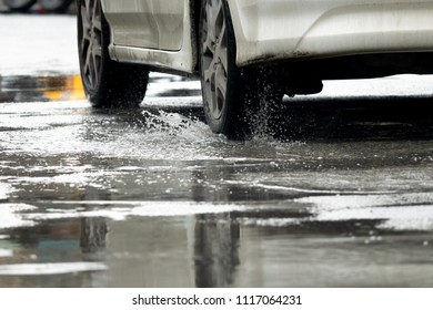 motion car rain big dirty puddle of water spray from the wheels, dangerous for driving.