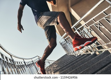 In motion. Close up of young African man in sports clothing running down the stairs while exercising outdoors