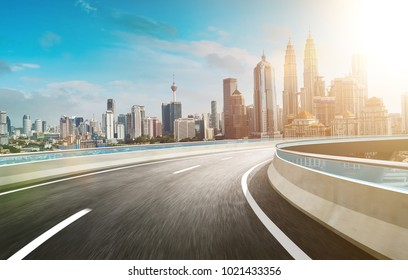Motion curvy flyover asphalt highway road with modern cityscape skyline view  . Sunrise scene .