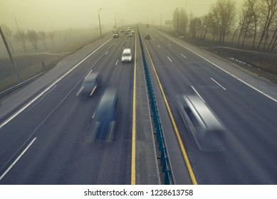 Сars in motion driving in the fog and mist. Bad driving conditions. Dangerous situation on the road. Foggy gray road, cars and trucks driving fading into the thick fog. Low visibility. Smoke on road
