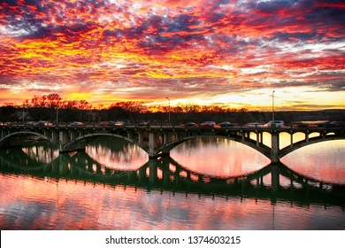 Motion image of heavy traffic in Austin, Texas Lamar boulevard bridge at sunset time. Beautiful dramatic sky at sunset reflected in Colorado river, downtown Austin.