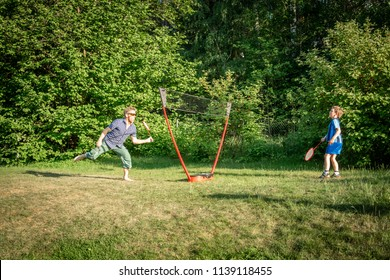 Motion of one adult male and a young boy playing badminton otudoors on a lawn with trees in the background.